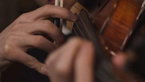 Close-Up-Hands-Of-Male-Violinist-Plucking-Strings-On-Violin