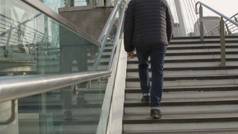 Man-Walking-Up-Steps-At-Embankment-London