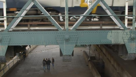 Pedestrians-Walking-Under-Bridge-With-Train-Passing-Above