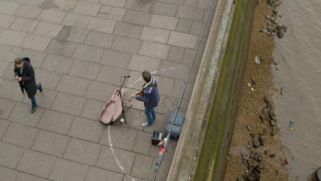 Overhead-of-Street-Musician-And-Passing-Pedestrian