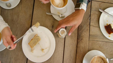 Overhead-View-Of-Hands-Lifting-Cups-Of-Coffee-And-Cake-Off-Cafe-Table