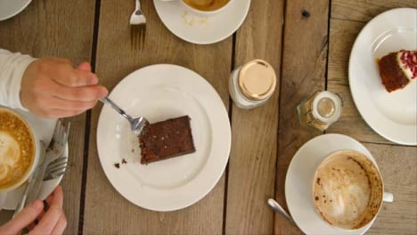 Overhead-Pan-Of-Hands-Lifting-Coffee-Mugs-And-Cake-Off-Cafe-Table