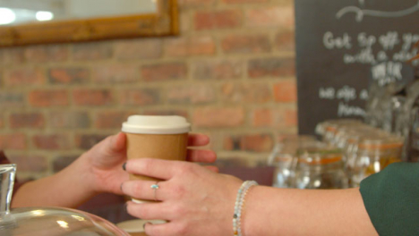 Handing-Coffee-to-Customer-in-Cafe-01