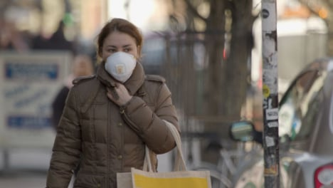 Woman-wearing-face-mask-and-coat-walking-on-street