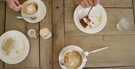 Overhead-View-Of-Hands-Lifting-Coffee-Mugs-And-Cake-Off-Cafe-Table