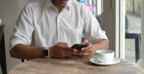 Male-customer-sitting-in-cafe-using-smartphone-mid-section