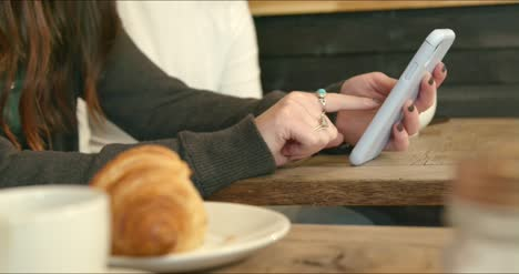 Woman-Using-Phone-in-Cafe