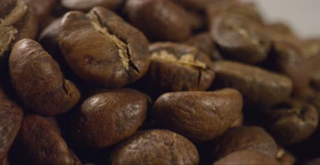 Macro-Close-Up-of-Coffee-Beans-Moving-Past-Camera