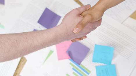 Overhead-close-up-of-business-colleagues-shaking-hands-over-paperwork-on-table