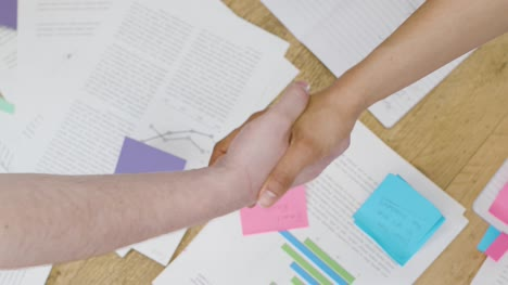 Overhead-close-up-colleagues-shaking-hands-over-paperwork-on-table