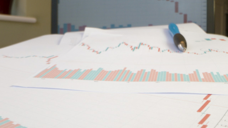 Close-Up-Stock-Charts-on-Paper-and-Laptop