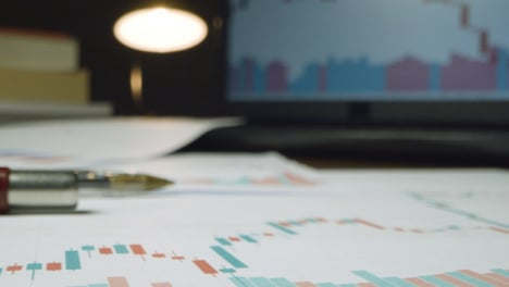 Close-Up-Stock-Market-Graphs-on-Desk-at-Night