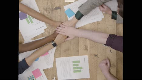 Overhead-View-Colleagues-At-Table-Stacking-Hands