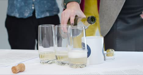 Close-Up-Pouring-Champagne-Into-Cups-And-Glasses-In-Office