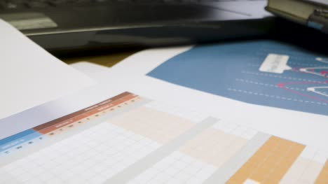 Close-Up-Project-Management-Printouts-on-Desk-With-Cup