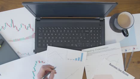 Overhead-Male-Hands-Making-Notes-on-Line-Chart-at-Desk