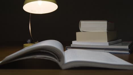 Pull-Focus-Open-Book-to-Stack-of-Books-on-Table