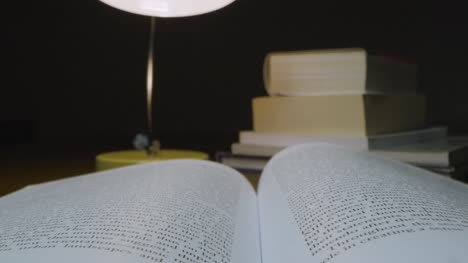 Tracking-Out-Close-Up-of-Open-Book-on-Table