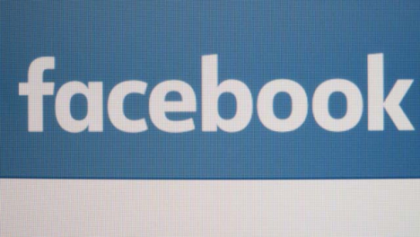 Close-Up-Pan-of-Facebook-logo-on-screen