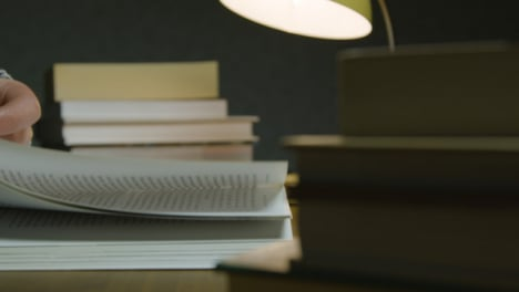Close-Up-Book-Stack-And-Male-Reading