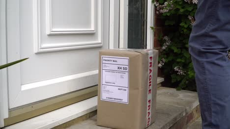 Male-Courier-Placing-Parcel-On-Doorstep