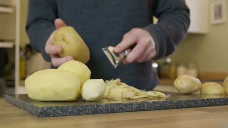 Tracking-In-Man-Peeling-Potatoes-in-Kitchen