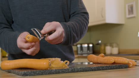 Man-Peeling-Carrots-in-Kitchen