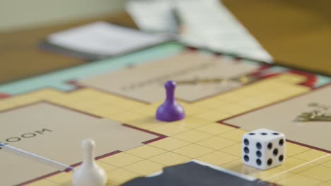 Close-Up-Hand-Rolling-Die-in-Cluedo-Board-Game