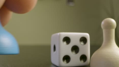 Close-Up-Rolling-Die-and-Moving-Pawn-in-Board-Game