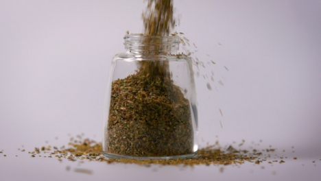 Slow-Motion-Close-Up-Oregano-Powder-Pouring-In-Jar