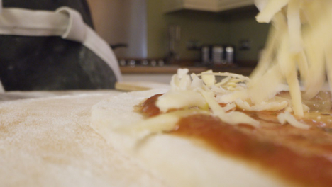 Close-Up-Sprinkling-Cheese-on-Pizza-Dough