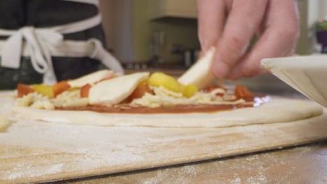 Close-Up-Putting-Mozzarella-on-Pizza-Dough
