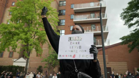 London-BLM-Protestor-Holding-Sign-in-Air-With-Raised-Fist