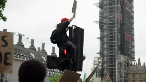 London-Black-Lives-Matter-Protester-Sitting-Above-Crowds-On-Traffic-Light