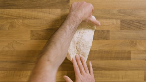 Top-View-Kneading-a-Sticky-Dough-on-Worktop