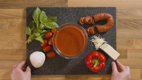 Top-View-Male-Placing-Ingredients-Board-on-Worktop