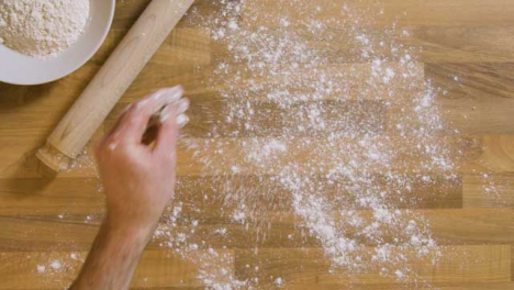 Top-View-Male-Sprinkling-Flour-on-Worktop