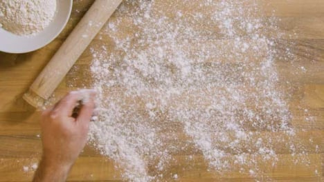 Top-View-Male-Sprinkles-Flour-on-Worktop