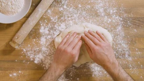 Top-View-Male-Flattens-Dough-on-Flour-Covered-Worktop