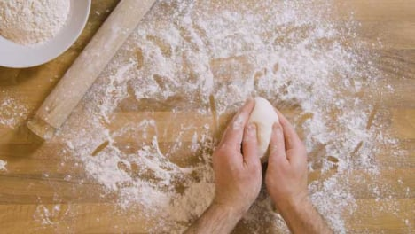 Top-View-Male-Sprinkles-Flour-on-Dough-and-Worktop-
