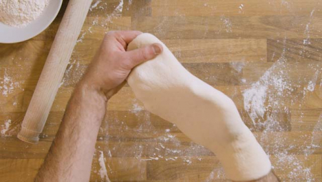 Top-View-Male-Stretches-and-Shapes-Pizza-Dough-