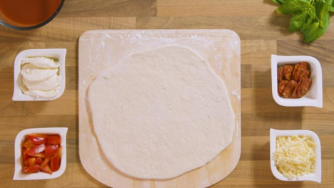 Top-View-Pizza-Dough-on-Peel-Placed-on-Worktop