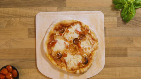 Top-View-Cooked-Pizza-on-Peel-Placed-on-Worktop