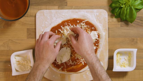 Top-View-Male-Placing-Mozzarella-on-Pizza