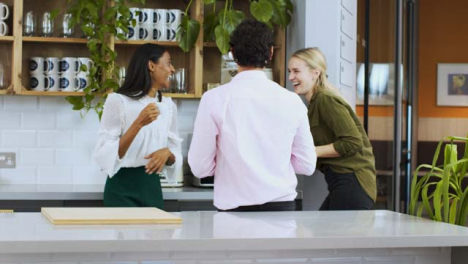Medium-Panning-Shot-Woman-Joining-Colleagues-On-Tea-Break