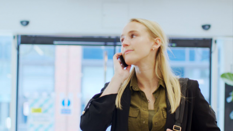 Tracking-Shot-of-Woman-On-Phone-Walking-Through-Corporate-Lobby