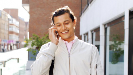 Tracking-Shot-of-Man-On-Phone-Walking-Outside-of-Office-Building-