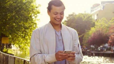 Tracking-Shot-of-Man-Texting-and-Enjoying-Walk-by-Canal