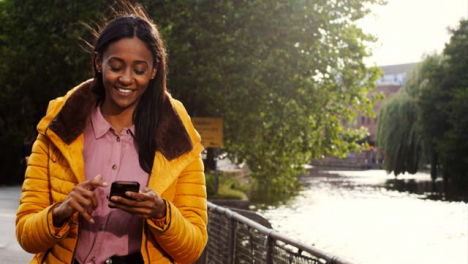Tracking-Shot-of-Woman-Texting-and-Enjoying-Walk-by-Canal