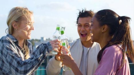 Close-Up-of-3-Friends-Enjoying-a-Drink-On-a-City-Roof-Terrace